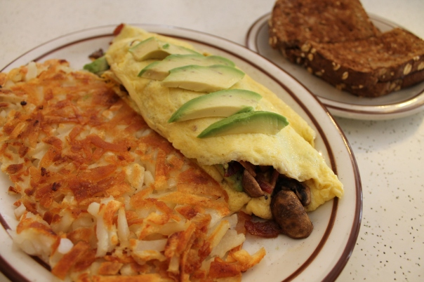 spinach, mushroom, bacon, avocado, and cheese omelet